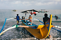 Local fishermen push their boat out to sea near the Holiday Inn Resort Baruna in Bali, Indonesia.