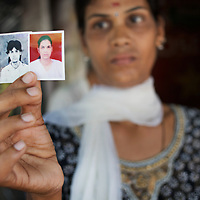 A transgender displays a portrait depicting herself before and after making the transition from life as a man...India's transexual community has a recorded history of more than four thousand years. Many consider the The Third Sex, also known as Aravanis, to posses special powers allowing them to determine the fate of others. As such, they are not only revered but despised and feared too. Resigned to the fringes of society, segregated and excluded from most occupations, many Aravanis are forced to turn to begging and sex work in order to earn a living. ..The annual transgender festival in the village of Koovagam, near Vilappuram, offers an escape from this often desolate existence. For some, the week-long partying and frenetic sex trade that culminates in the Koovagam festival is about fulfilling lustful desires. For others, the gathering provides a chance for transgenders to bond, share experiences, join the wider homosexual gay-community and coordinate their campaign for recognition and tackle the challenge of HIV/AIDS. ..It is the Indian state of Tamil Nadu that the eighty-thousand-strong Aravani community has made advances in their fight for rights. In 2009, the Tamil Nadu state government began providing sex-change surgery free of cost. The state has also offers special third-gender ration cards, passports and reserved seats in colleges. And 2008 the launch of Ippudikku Rose, a Tamil talk-show fronted by India's first transgender TV-host and the release of a mainstream Tamil film staring an Aravani in the lead-role. ..These advances clearly signal a victory for south India's transgenders, but they have also exposed deep divisions within the community. There is a very real gulf that separates the majority poor from their potentially influential but often reticent, upper-class sisters. ..Photo: Tom Pietrasik.Chennai, Tamil Nadu. India.May 2009