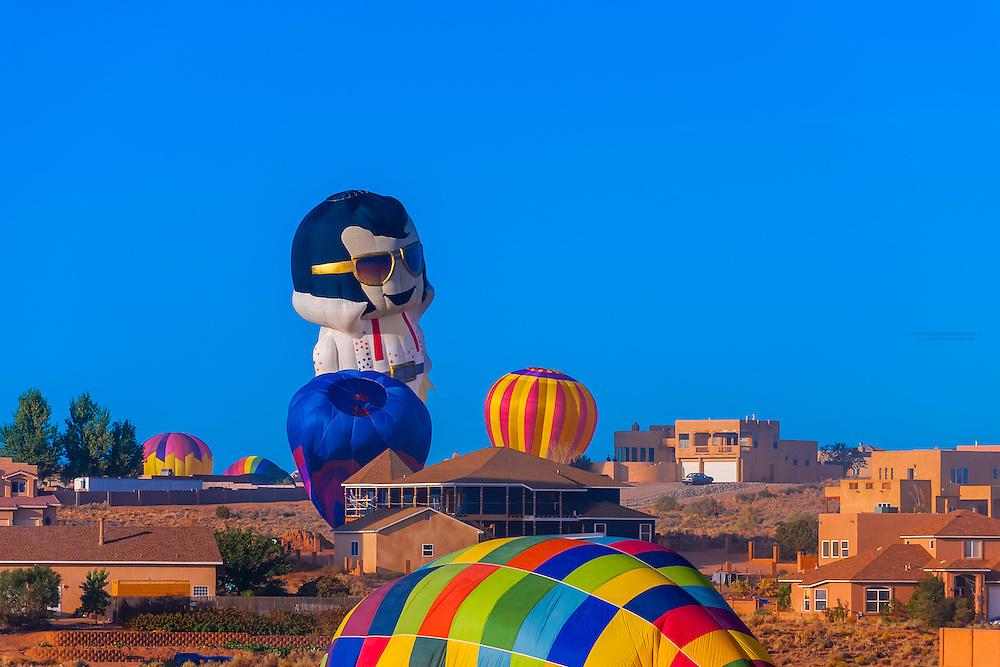 Hot air balloons landing in a neighborhood, including a special shape balloon called Aaron (Elvis' middle name) at the Albuquerque International Balloon Fiesta, Albuquerque, New Mexico USA
