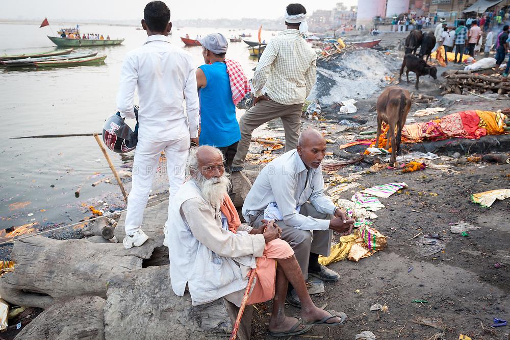 Family members wait during the burning of a body at Manikarnika cremation ground, Varanasi, India. Photo ©robertvansluis.com