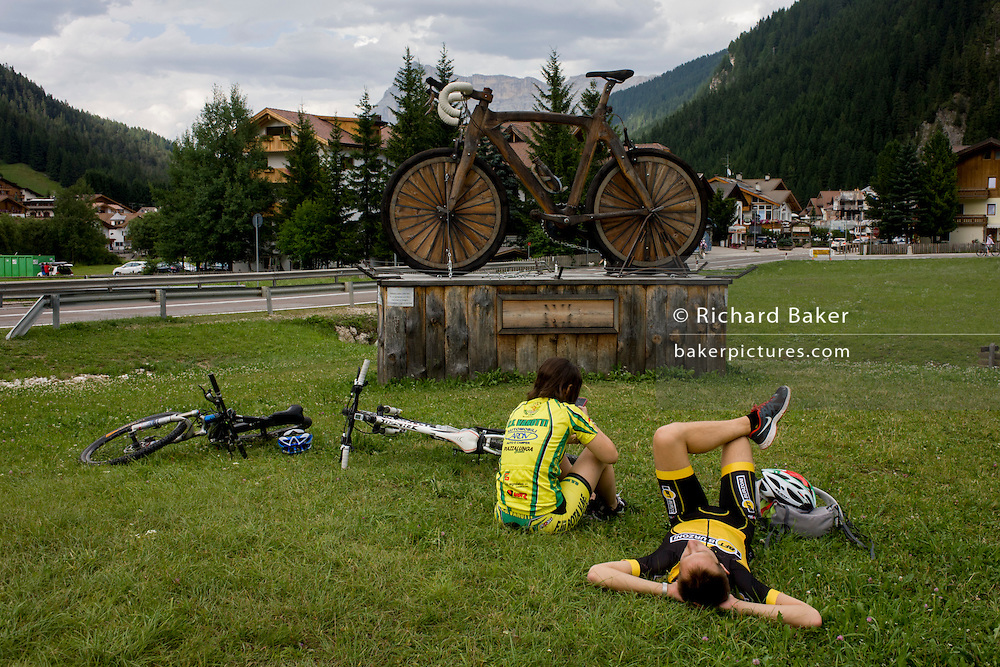 Cyclists rest by a large wooden mountain bike sculpture in the town of Corvara during the summer walking season in south Tyrol, northern Italy.