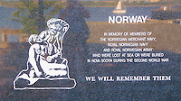Norway Memorial in Halifax, Nova Scotia. Image taken with a Leica V-Lux 30 camera (ISO 125, 13.6 mm, f/4.7, 1/80 sec). The image includes the reflection of the photographer, Halifax Harbor, and a sailboat.