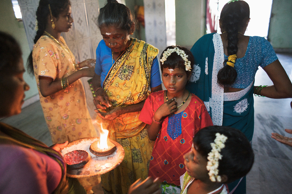 Anjalakshi, age 9, (in red) visits a temple in Pudupettai to mark the Hindu festival of Diwali. She is accompanied by their sisters and maternal grandmother Chitra (yellow sari). The Krishnamurthy sisters spent the Diwali weekend visiting relatives while staying with their father in their home town of Puddupettai. <br /><br />The five Krishnamurthy sisters from Pudupettai in Tamil Nadu lost their mother to the 2004 Asian Tsunami. Their father declared himself unable to raise his daughters and, like many other tsunami widowers, placed them in the care of a government orphanage. He has since remarried. The sisters, now aged between 6 and 14, have lived with 120 other orphaned children in Cuddalore's Government Home for Tsunami Children since January 2005. Though of course the detail of their lives is unique, the Krishnamurthy sisters share many experiences with other tsunami-orphans in Tamil Nadu and across the tsunami-affected region. <br /><br />According to staff at the government home, Sivaranjini, age 14, has begun to loose interest in her studies. She fared badly in recent examinations which staff attribute to the poor education she received before the tsunami. The other four sisters are doing well at school. Sivaranjini continues to be a very committed elder sister, undertaking many of a tasks for which a mother would normally be responsible. Sivaranjini washes her sisters' clothes, helps with their studies, offers affection and, when appropriate, administers punishment. <br /><br />Krishnamurthy, the sisters father, visits the orphange once or twice a month. His sister Kamasala visits more regularly but reserves most of her attention for Sivapriya, age 12. Sivapriya used to live with her paternal aunt before the tsunami. Like other children at the orphange, the five sisters also spend religious festivals and the annual school holidays with their father and extended family. During these periods the Krishnamurthy sisters are treated to gifts and lavished attenti