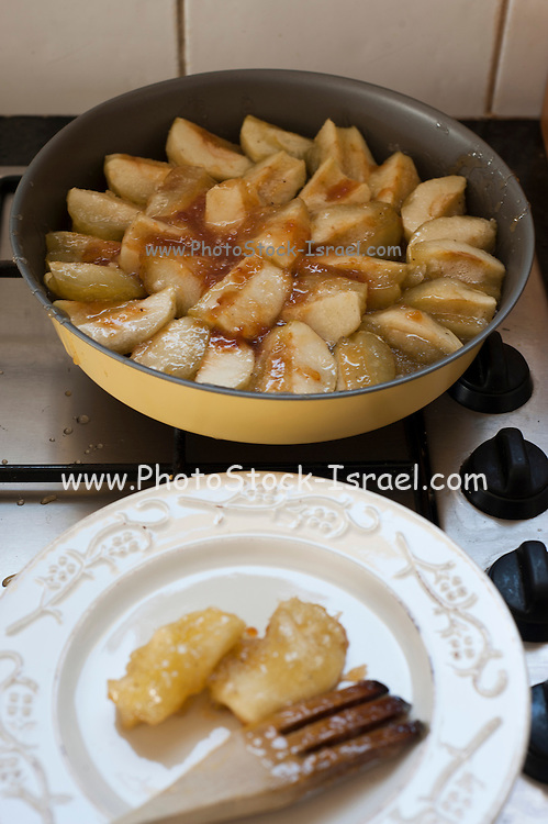 Tarte Tatin an upside-down apple tart in which the apples are caramelized in butter and sugar before the tart is baked. Apples are being caramelized with sugar and butter