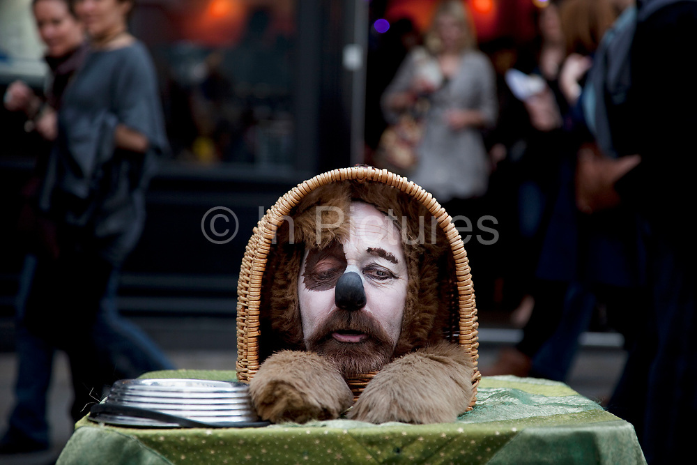 Street performer acts as a humourous dog. Collecting money whilst making fun and talking to his audience. Covent Garden in the West End of London.