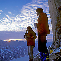 BAFFIN ISLAND,  Nunavut, Canada. Alex Lowe & John Catto (MR) relax after long day climbing on Great Sail Peak, an Arctic big wall climb above frozen lake in Stewart Valley.