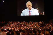 Chairman of Ernst & Young Mark Ottey peers down on his employees on a giant screen, addressing his loyal audience of E & Y staff who have congregated at an Ernst & Young Academy Day held for 3,000 of company London employees at Excel in London's Docklands, England. The hall is packed and his disciples listen and watch intently and obediently to watch their Leader speak like a Big Brother character, who ernestly and sincerely talks down to them despite being dressed casually for such a large event. Each employee will attend this brainstorming fair where later, motivational pep-talks from executives, outside speakers and gurus will talk to large groups of E & Y personnel so their presence on this day away from the office is vital for the year's business ahead.