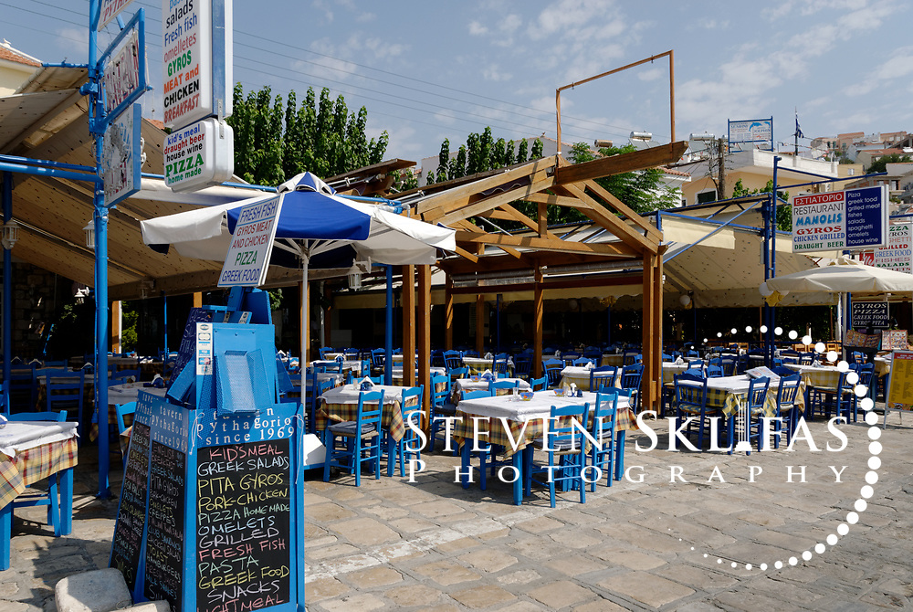 Samos. Greece. View of typical Greek island restaurant with menu displayed at its front along the Pythagoreio waterfront which is filled with restaurants, cafes and bars and has colourful fishing boats docked in its pretty harbour. The town of Pythagoreio is the most popular and fashionable town on the island and was named after the great philosopher Pythaogaras who was born here in 580 BC.