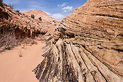 Entrance to Tunnel Slot Canyon, Grand Staircase Escalante National Monument, Utah, USA. Directions to unmarked trailhead for Zebra and Tunnel Slot Canyons: From Escalante town, drive 6 miles east on Highway 12, turn right on Hole-in-the-Rock Road, drive 7.8 miles to the third cattle guard and park on west side of road. Hike east on well-trodden but unmarked path, 5 miles round trip to Zebra Slot, plus an optional 3 miles round trip to Tunnel Slot (750 feet gain over 8 miles), using map from GSENM Visitor Center or canyoneeringusa.com.