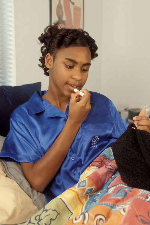 African-American teenage girl, 13, applying lip balm to lips while in pajamas in bed. Model Release<br /> ©Bob Daemmrich