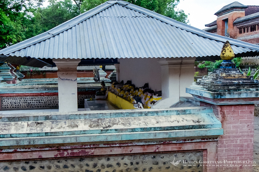 Nusa Tenggara, Lombok, Mataram. Pura Lingsar, under this roof in the Wektu Telu section you can see some sacred volcanic rocks dressed in yellow textiles.