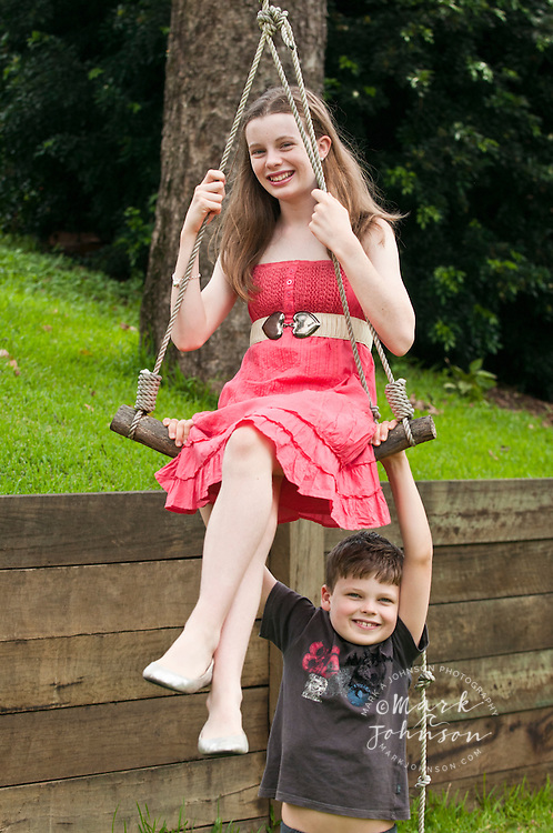 Brother & sister, playing with rope swing in backyard