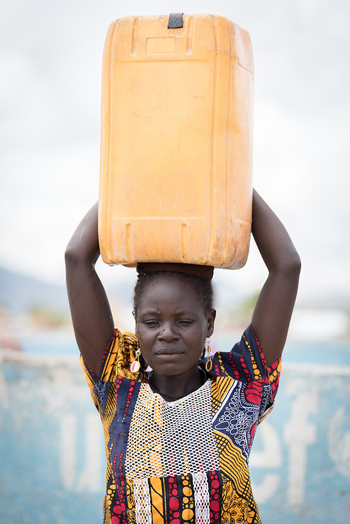 30 May 2019, Mokolo, Cameroon: A woman carries water from one of the boreholes through which the Lutheran World Federation's World Service programme supplies drinking water to refugees in Minawao. The Minawao camp for Nigerian refugees, located in the Far North region of Cameroon, hosts some 58,000 refugees from North East Nigeria. The refugees are supported by the Lutheran World Federation, together with a range of partners.