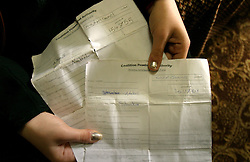 An Iraqi girl holds the Detainee Information Request Forms for her father and brother, Bahgdad, Iraq, Feb. 22, 2004. The girl said she paid a $25,000 bribe to several Americans in civilian clothes who were carrying weapons, to erase the criminal records of her father and brother who are in prison at Abu Ghraib. She also said an American soldier struck her with the butt of his machine gun as he entered their apartment during a raid of their home.