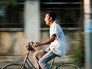 A local, tired man cycling through the streets of Siem Reap, Cambodia
