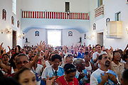 Worshippers in a church. Often the lines between Candomble and Catholicism are blurred. This is especially true with the Sao Lazaro event in late January in Salvador de Bahia, seen as the home of Candomble. Sao Lazaro represents healing and the sick.
