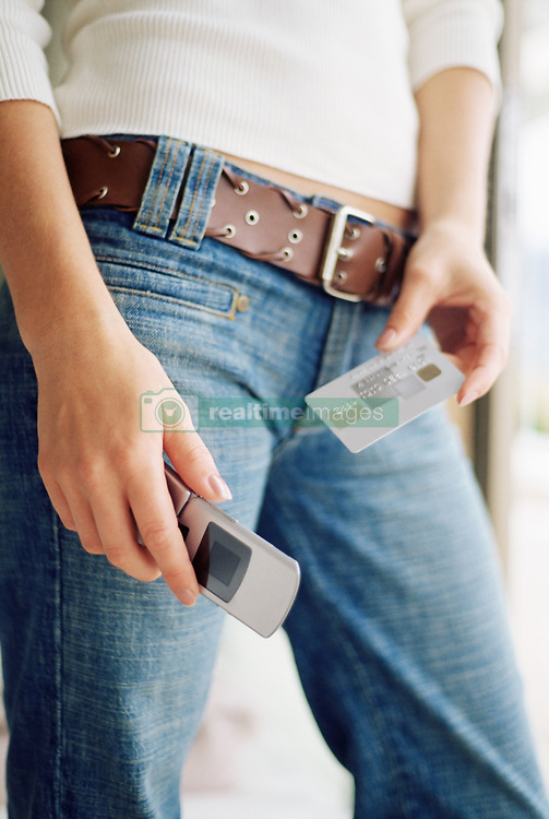Dec. 14, 2012 - Woman with mobile phone and credit card (Credit Image: © Image Source/ZUMAPRESS.com)