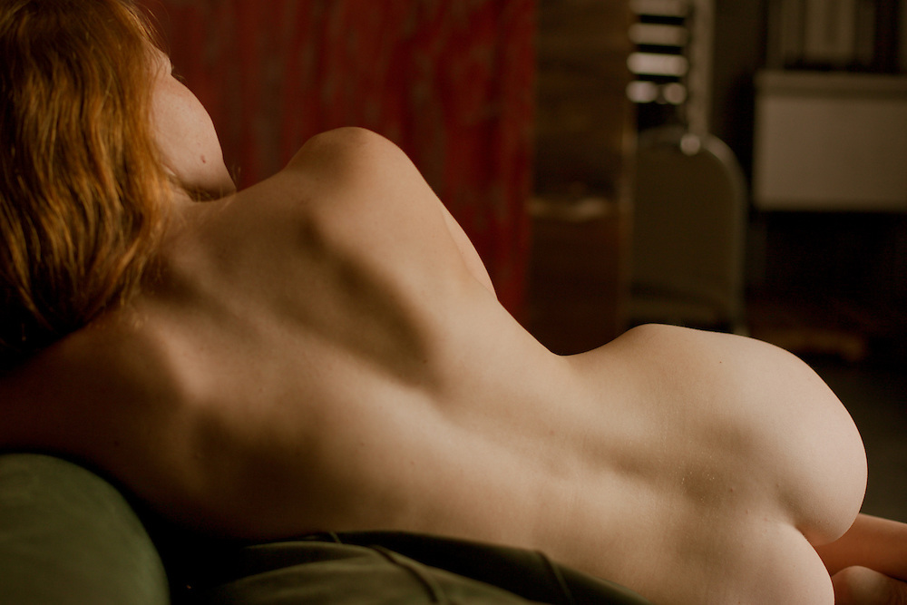 Fine art photography of beautiful nude redhead model with porcelain skin in natural light.