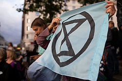 © Licensed to London News Pictures. 06/10/2019. London, UK. An Extinction Rebellion protester holds a flag at Marble Arch as protesters gather to mark the beginning of two weeks of direct action in London. Photo credit: George Cracknell Wright/LNP
