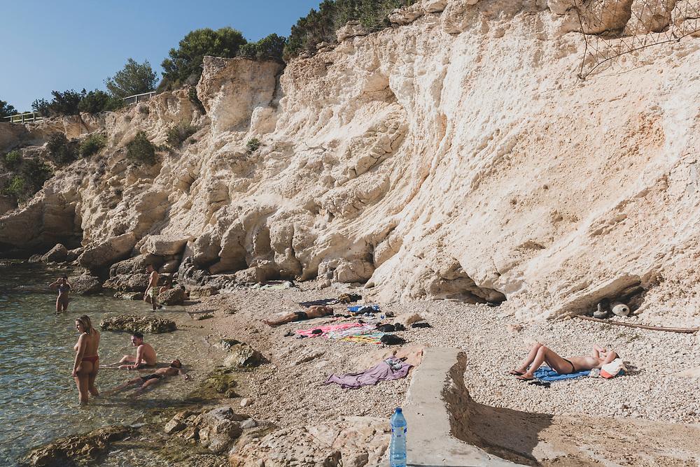 Sant Antoni de Portmany, Ibiza, Spain - July 30, 2018: People sunbathe and swim at  a small cove on the Mediterranean Sea near Sant Antoni (San Antonio), Ibiza.