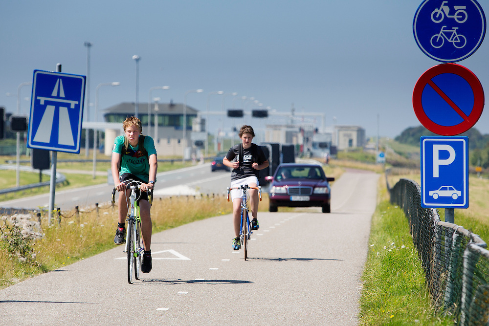 Fietsers rijden over de Afsluitdijk. In 1932 werd de opening tussen de Waddenzee en de toenmalige Zuiderzee gesloten. Nu is het een belangrijke verkeersader tussen Friesland en Noord-Holland en scheidt het de Waddenzee met het IJsselmeer.<br /> <br /> Cyclists are riding on the Afsluitdijk. In 1932, the gap between the Wadden Sea and the former Zuiderzee closed by the Afsluitdijk. Now it is a major thoroughfare between Friesland and North Holland and it separates the Wadden Sea from the IJsselmeer.