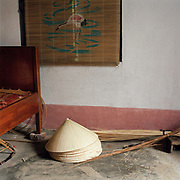 Interior of a home in Phu My conical hat making village, Ha Tay province, Vietnam. With Vietnam's growing population making less land available for farmers to work, families unable to sustain themselves are turning to the creation of various products in rural areas.  These 'craft' villages specialise in a single product or activity, anything from palm leaf hats to incense sticks, or from noodle making to snake-catching. Some of these 'craft' villages date back hundreds of years, whilst others are a more recent response to enable rural farmers to earn much needed extra income.
