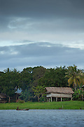 Canoe passes in front of Lakeside wooden huts, Lake Murray, Middle Fly District, Western Province, Papua New Guinea