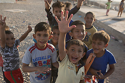 Licensed to London News Pictures. 22/10/2016. Young Iraqi refugees wave to the camera at the Dibaga refugee camp near Makhmur, Iraq.<br />