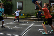 Friends, from left, Owen Tuohy, 11, Henry Souza, 12, Jaxson Marsh, 11, and Sawyer Hall, 11, play four square in Souza's Lebanon, N.H., driveway on Tuesday, June 1, 2021. The king in square four determines the rules of each round and the players try to knock their opponents out by bouncing the ball past them. After missing a ball a player returns to square one. (Valley News - James M. Patterson) Copyright Valley News. May not be reprinted or used online without permission. Send requests to permission@vnews.com.