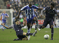 Photo: Dave Howarth.<br /> Wigan Athletic v Bolton Wanderers. Carling Cup.<br /> 20/12/2005.  Wigan's Jason Roberts battles past Bolton's Ricardo Gardiner and Abdoulaye Faye