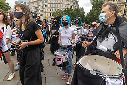 """Licensed to London News Pictures. 23/08/202. London, UK. A young climate change protester plays the drums as Extinction Rebellion (XR), arrive in Trafalgar Square, London for the start of a 14 day protest with disruptive action and possible occupations of buildings and services. The protest, """"The Impossible Rebellion"""", want the government to implement their demand to stop all new fossil fuel investment immediately. Photo credit: Alex Lentati/LNP"""