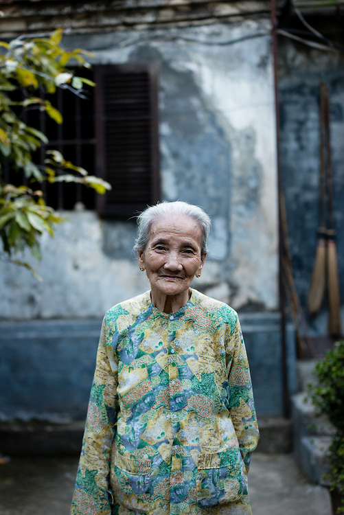 Vietnamese woman standing in front of her traditional home in Hue