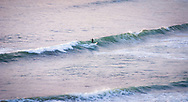 A surfer catches a sunset swell at a secret break on the California coast in Big Sur