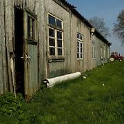 Nederland - Veendam - ( Groningen ) - 14-04-2009<br />De ' Veendammer Barak'  in het Lanschap bij Veendam, deze barak stond op Kamp Westerbork en deed dienst batterijensloperij.<br /><br />Barak 57<br /><br />Barak 57 was gebouwd om dienst te doen als werkbarak. In 1943 werd deze een tijd als woonbarak gebruikt. Mensen die direct op transport moesten, werden onder meer hierin ondergebracht. Eind augustus 1943 werd de '57' weer industriebarak. Hierin was de batterijsloperij gevestigd. Van dit smerige en ongezonde werk zijn in het voorjaar van 1944 filmopnamen gemaakt, die bewaard zijn gebleven. <br />Anne Frank en haar zusje Margot hebben een aantal weken in deze barak moeten werken.<br /><br />Evenals de rest van het kamp bleef deze barak na de bevrijding in gebruik. In 1957 werd nr. 57 verkocht om een nieuwe bestemming in Veendam te krijgen. De oorspronkelijk 84 m lange barak werd in tweeën gedeeld en de beide delen werden naast elkaar geplaatst. Aldus was het object geschikt als landbouwschuur, tot op heden.<br />Binnenkort zal deze 'Veendammer' barak worden gedemonteerd en naar het Herinneringscentrum worden overgebracht om te worden geconserveerd. Gedacht wordt om deze bijna zeventig jaar oude '57' weer een plek op de oorspronkelijke plaats te geven.<br /><br />In de op Harry Mulisch' boek gebaseerde film 'The discovery of heaven' figureert deze barak. <br />Foto: Sake Elzinga