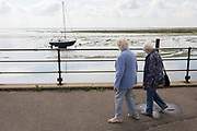 Two elderly ladies walk along the promenade where a single yacht sits upright in low-tide estuary mud at Old Leigh, on 10th September 2019, in Leigh-on-Sea, Essex, England.