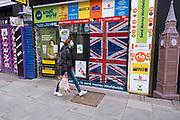 Woman wearing a face mask walks past shuttered closed money transfer shop along Oxford Street which is largely empty of shoppers as the national coronavirus lockdown three continues on 28th January 2021 in London, United Kingdom. Following the surge in cases over the Winter including a new UK variant of Covid-19, this nationwide lockdown advises all citizens to follow the message to stay at home, protect the NHS and save lives.