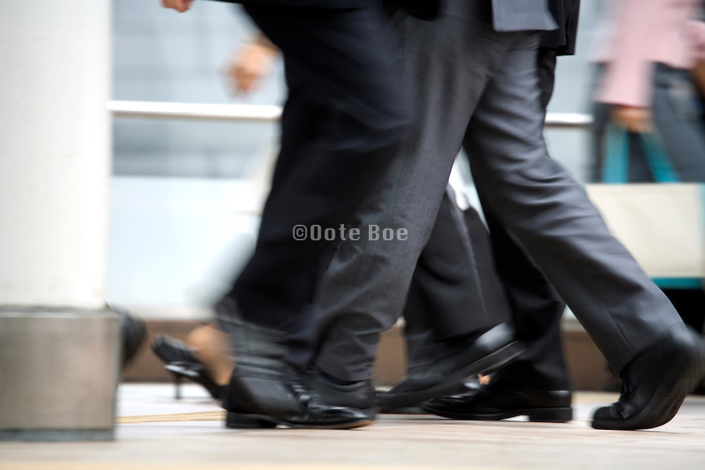 businesspeople walking with a businesswoman walking the opposite way