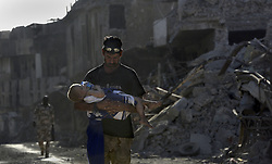 July 17, 2017 - Mosul, Iraq - An Iraqi Army soldier DRED SUBHI carries a little girl from the front line to a Trauma Stabilization Point with Iraqi Army medics on July 17, 2017 amid ruins of the Old City. She found by soldiers when they saw her walking naked in the rubble. She was believed to be a foreigner, her parents most likely ISIS fighters killed in the battle or by suicide bomb, it was difficult for medics to determine exactly. She was given medical care and water.  The soldiers said they saw other children but couldn't reach them as it was too dangerous with ISIS fighters nearby. The battle continued in a small part of West Mosul even though it was declared liberated a week ago.  Injuries from suicide bombers, grenades and snipers occurred as ISIS fighters use tunnels to continue the fierce conflict. (Credit Image: © Carol Guzy via ZUMA Wire)