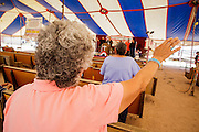 """14 JULY 2012 - FT DEFIANCE, AZ:   A woman raises her hand in praise during the """"Singspiration"""" gospel jam at the 23rd annual Navajo Nation Camp Meeting in Ft. Defiance, north of Window Rock, AZ, on the Navajo reservation. Preachers from across the Navajo Nation, and the western US, come to Navajo Nation Camp Meeting to preach an evangelical form of Christianity. Evangelical Christians make up a growing part of the reservation - there are now more than a hundred camp meetings and tent revivals on the reservation every year. The camp meeting in Ft. Defiance draws nearly 200 people each night of its six day run. Many of the attendees convert to evangelical Christianity from traditional Navajo beliefs, Catholicism or Mormonism. """"Camp meetings"""" are a form of Protestant Christian religious services originating in Britain and once common in rural parts of the United States. People would travel a great distance to a particular site to camp out, listen to itinerant preachers, and pray. This suited the rural life, before cars and highways were common, because rural areas often lacked traditional churches.  PHOTO BY JACK KURTZ"""