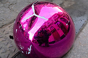 A detail of a split pink plastic sphere which has come to rest in the gutter on a side street in central London, on 23rd February 2021, in London, England.