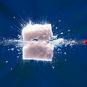Sugar Cube exploding with bullet going through it on a blue background. Ray Massey is an established, award winning, UK professional photographer, shooting creative advertising and editorial images from his stunning studio in a converted church in Camden Town, London NW1. Ray Massey specialises in drinks and liquids, still life and hands, product, gymnastics, special effects (sfx) and location photography. He is particularly known for dynamic high speed action shots of pours, bubbles, splashes and explosions in beers, champagnes, sodas, cocktails and beverages of all descriptions, as well as perfumes, paint, ink, water – even ice! Ray Massey works throughout the world with advertising agencies, designers, design groups, PR companies and directly with clients. He regularly manages the entire creative process, including post-production composition, manipulation and retouching, working with his team of retouchers to produce final images ready for publication.