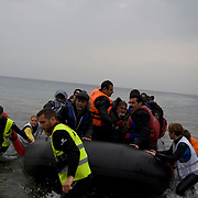Volunteers help a group of about 60 migrants land at a beach outside Mytilene in Lesbos island, Greece.