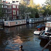 Amsterdamse gracht met woningen en woonboten