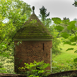 Round brick building with green foliage at the entrance to the Williamsburg historic complex.