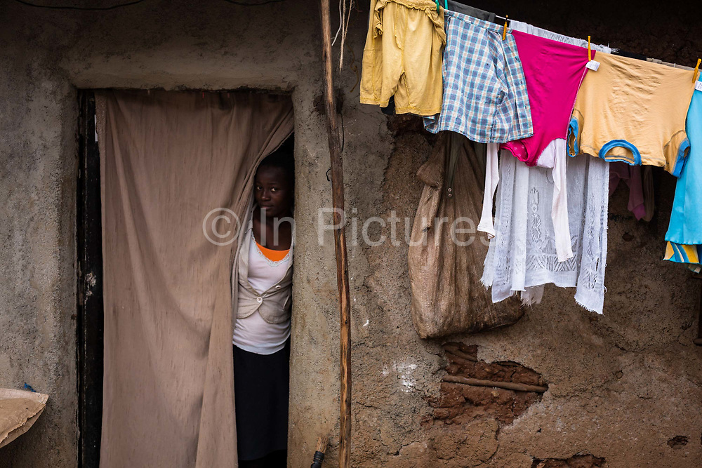 A young woman looks out of her home inside Kibera Slum, Nairobi. Considered to be the largest slum in Africa with a population close to 1 million people. The living conditions in it  are considered of extreme poverty with most housholds having no runing water or sanitation. The population is made up of all ethno-linguistic groups of Kenya drawing many residents from the poorest rural backgrounds.