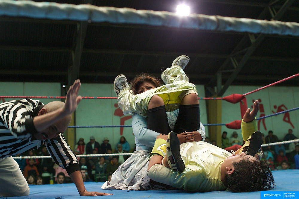 Cholita Carmen Rosa pins down her male opponent during the 'Titans of the Ring' wrestling group performance at El Alto's Multifunctional Centre. Bolivia. The wrestling group includes the fighting Cholitas, a group of Indigenous Female Lucha Libra wrestlers who fight the men as well as each other for just a few dollars appearance money. El Alto, Bolivia, 24th January 2010. Photo Tim Clayton