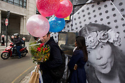 A man carries a bunch of birthday balloons and red flowers past a construction hoarding. Featuring a surprised expression of a woman reproduced in black and white, the man stops to let a moped scotter pass and he grasps the bouquet for his wife's special day. The hoarding is located on Ludgate Hill in the City of London, the capital's financial financial heart and historic centre founded by the Romans in AD43 but now the point of focus for Britain's economy.