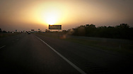 A highway sign along four-lane US 287 with smoke in the air from grass wildfires, the sun dimmed by the smoke is low in the sky. west Texas, USA