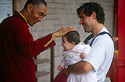 A visiting Lama teacher of Kagyu Tibetan-Buddhism greets westerner baby in the Kagyu Samye Ling Buddhist retreat centre