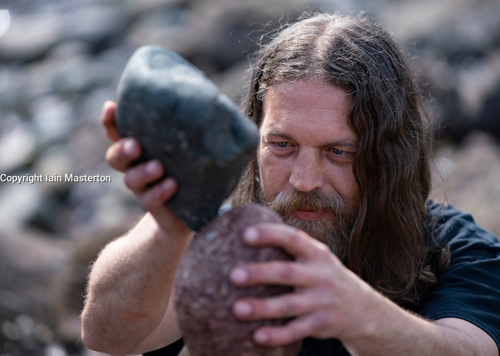 Dunbar, Scotland, UK. 20 April, 2019. Kev Potts working on his stone sculpture on Eye Cave beach in Dunbar during opening day of the European Stone Stacking Championship 2019.